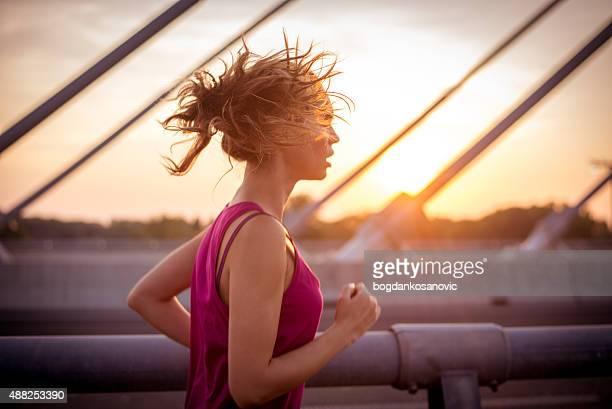 Female athlete running over the bridge in the morning