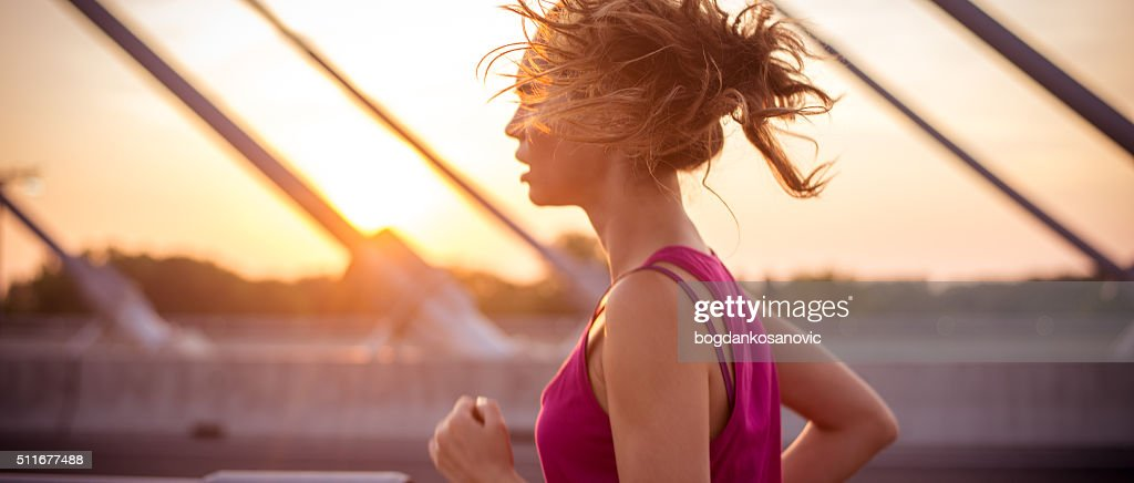 Female athlete running over the bridge in the morning : Stock Photo