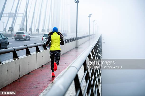 Female athlete running over the bridge