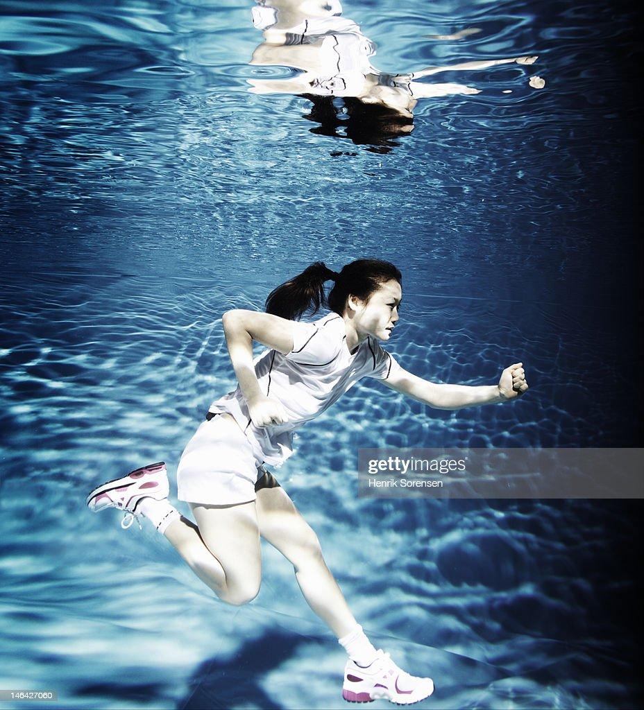 female athlete running under water : Foto de stock