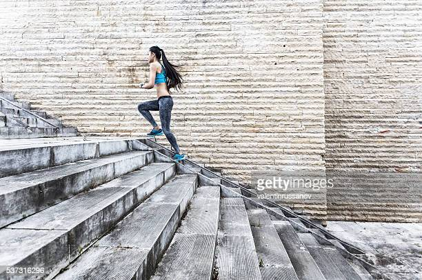 Female athlete running up on stairs-side view