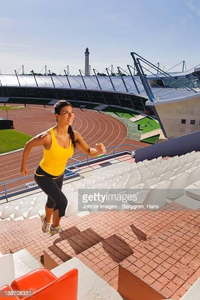 Female athlete running up stadium steps