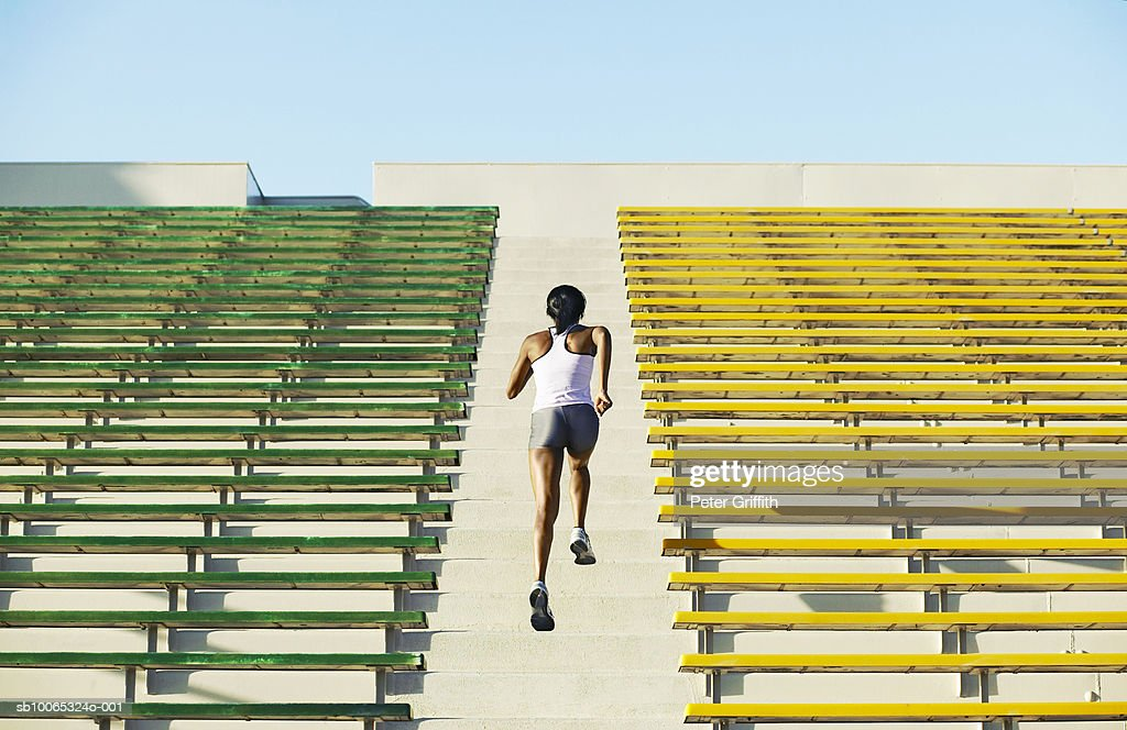 Female athlete running up stadium steps, rear view : Foto stock