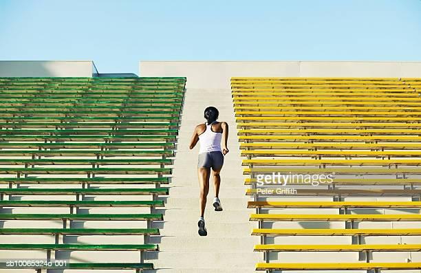 Female athlete running up stadium steps, rear view
