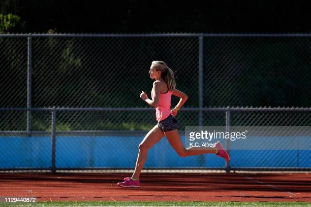 a female athlete runs on a track - running shorts stock pictures, royalty-free photos & images