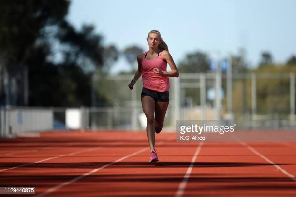 a female athlete runs on a track - running track stock pictures, royalty-free photos & images