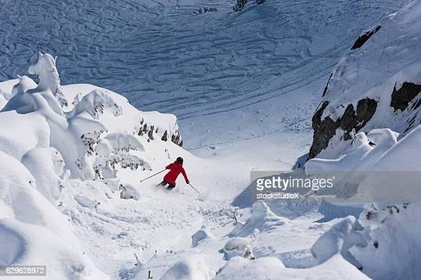 Female athlete skiing a chute