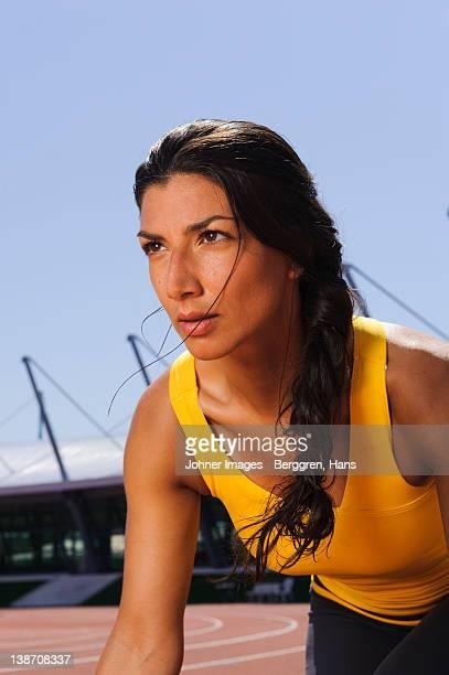 Female athlete sprinting at stadium