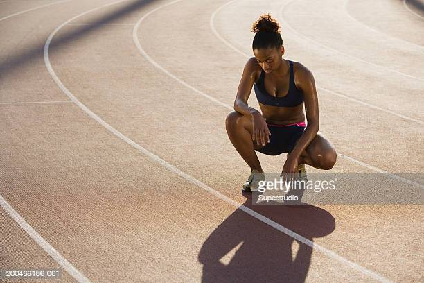 Female athlete squatting on track, looking downwards