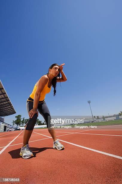 Female athlete standing at stadium