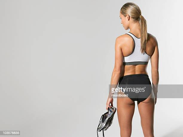 female athlete standing holding shoes, back view - haar naar achteren stockfoto's en -beelden