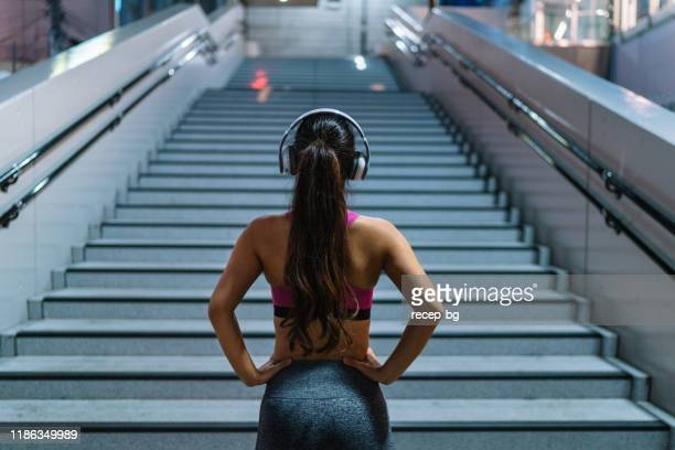 female athlete standing in front of stairs - extra long stock pictures, royalty-free photos & images