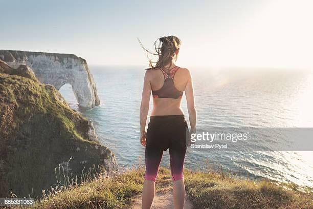 Female athlete standing on edge of cliff