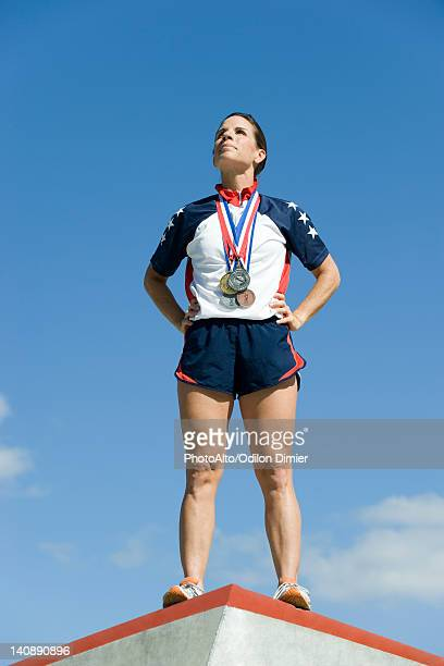female athlete standing on winner's podium - winners podium stock-fotos und bilder