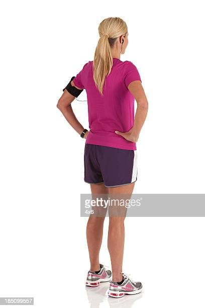 Female athlete standing with arms akimbo