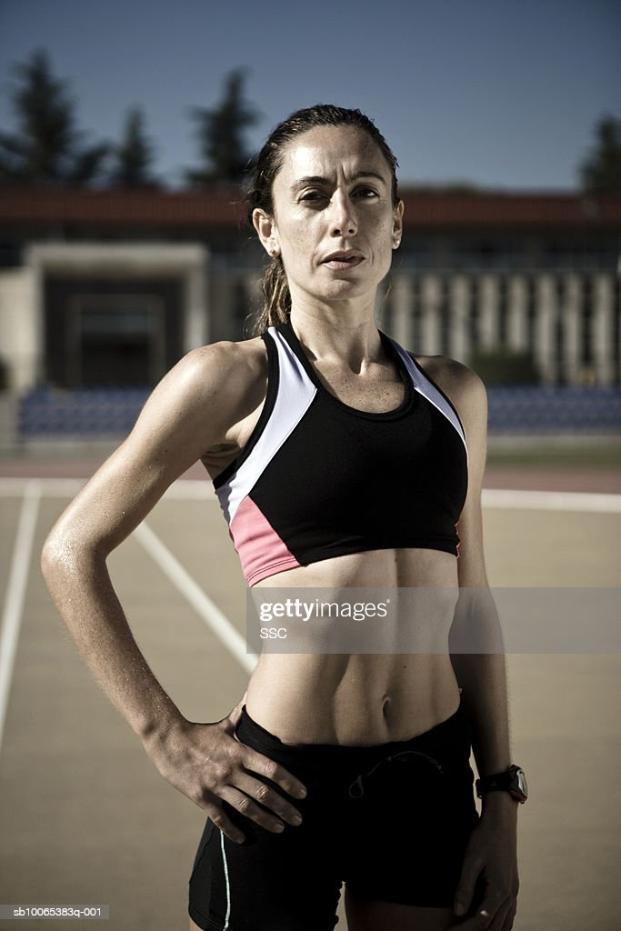 Female athlete standing with hand on hip in stadium, portrait, close-up : Foto stock