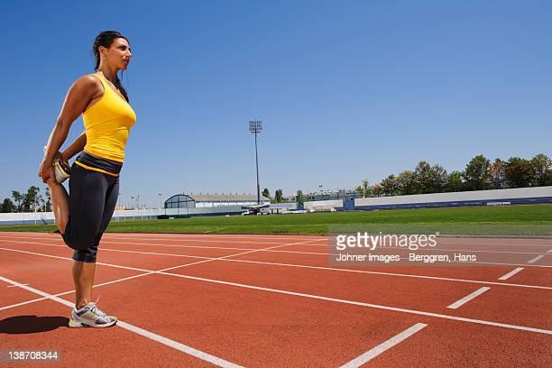 Female athlete stretching at stadium