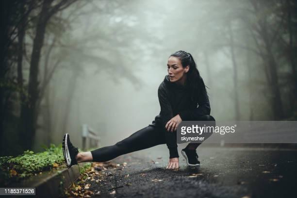 sportlerin streckt ihr bein an regnerischen tagen in nisty natur. - winter sport stock-fotos und bilder