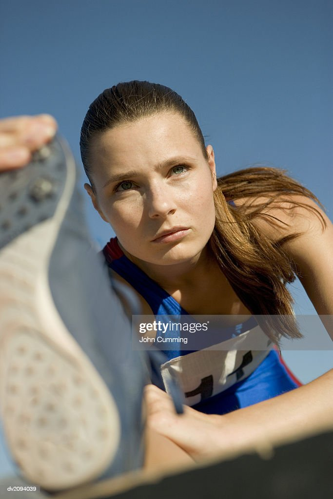 Female Athlete Stretching Her Legs : Stock Photo