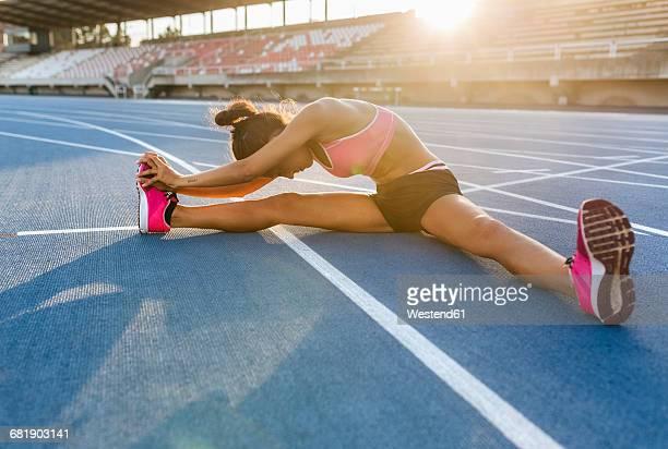 female athlete stretching in stadium - aufwärmen stock-fotos und bilder