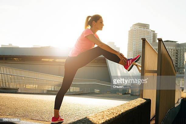 Female athlete stretching in sunset in city of Osaka, Japan