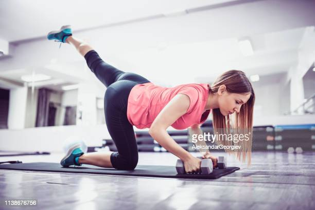 female athlete stretching on mat - aleksandar georgiev stock photos and pictures
