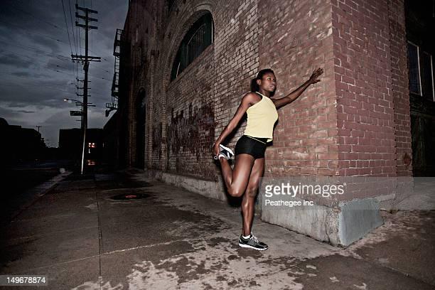 Female athlete stretching on sidewalk