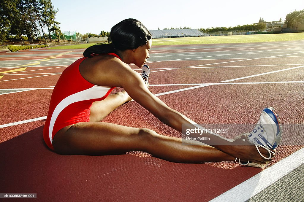 Female athlete stretching on track : Foto stock