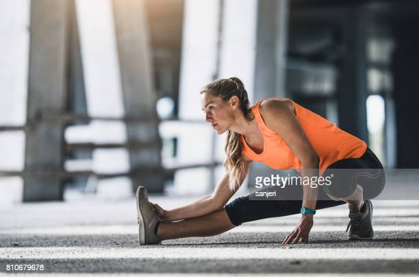 female athlete stretching outdoors - warming up stock pictures, royalty-free photos & images