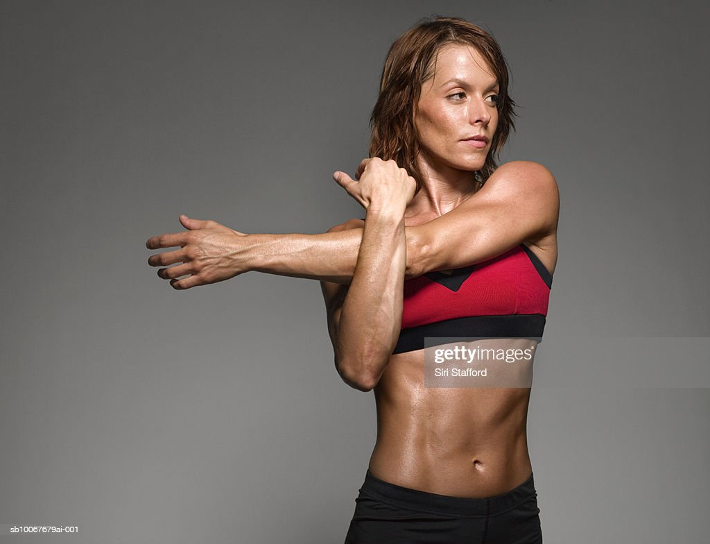 Female athlete stretching, studio shot : Stock Photo
