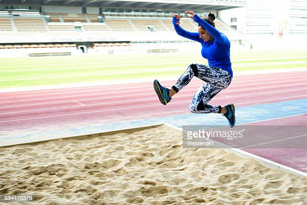 Female athlete training for long jump in stadium