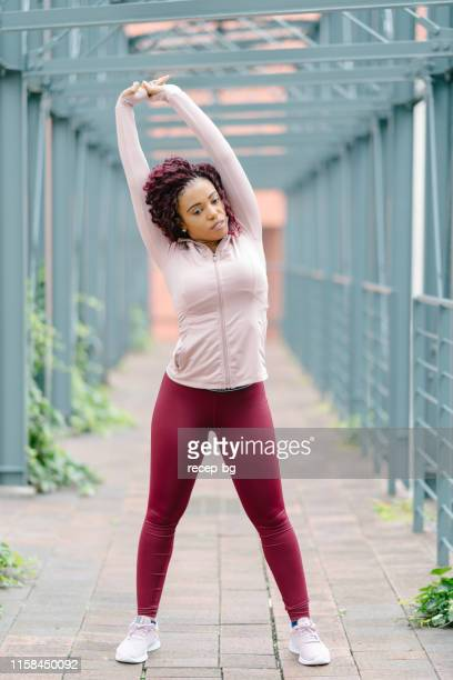 female athlete warming up for sports practicing - curvy asian woman stock pictures, royalty-free photos & images