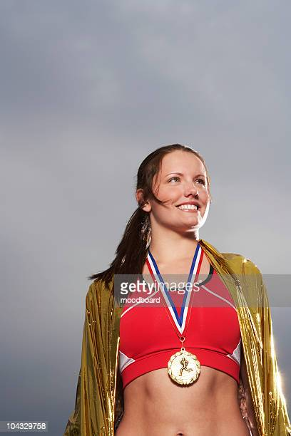 Female athlete wearing gold medal, low angle view, portrait