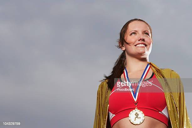 female athlete wearing gold medal, low angle view, portrait - gold medal stock pictures, royalty-free photos & images
