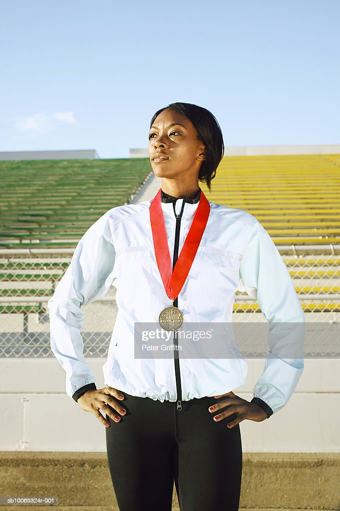 Female athlete wearing medal in stadium : Foto stock