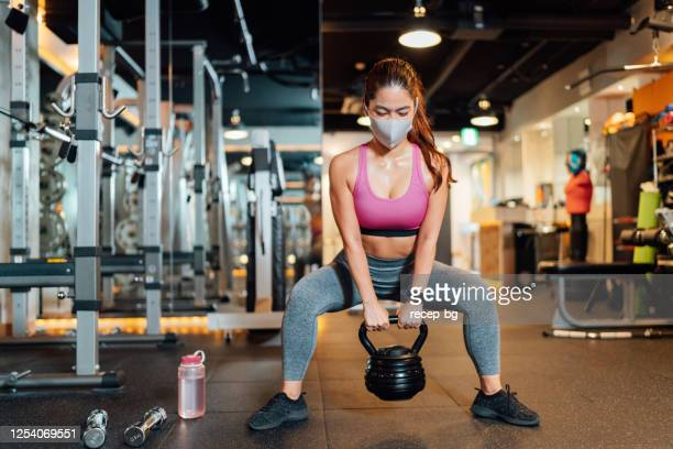 female athlete wearing protective face mask and lifting kettlebell in gym - crouching stock pictures, royalty-free photos & images
