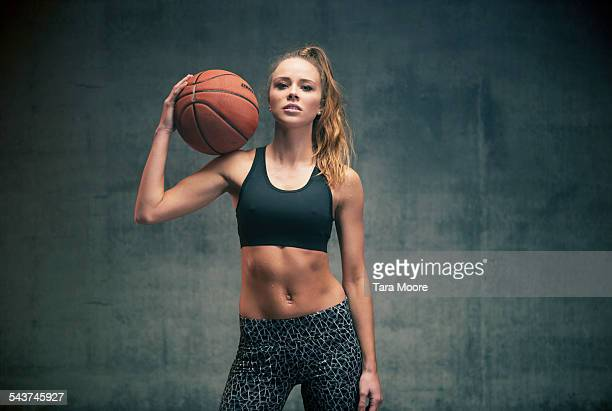 Female athlete with basketball concrete background