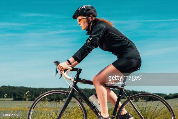 Female athlete with cycling helmet rides her bicycle on rural road