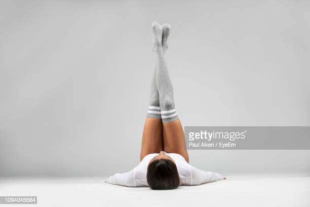 female athlete with feet up lying against white background - aikāne stock pictures, royalty-free photos & images