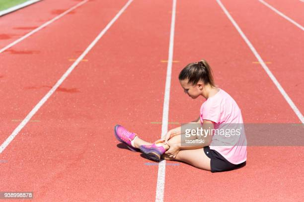 female athlete with pain  on running track - tendon stock photos and pictures