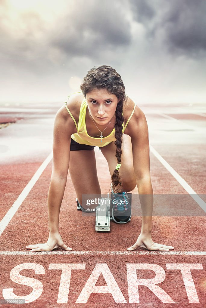 Female athlete with yellow too in the starting blocks : Stock Photo