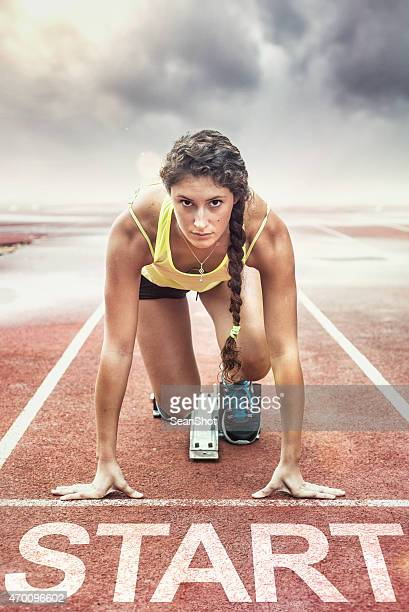 Female athlete with yellow too in the starting blocks