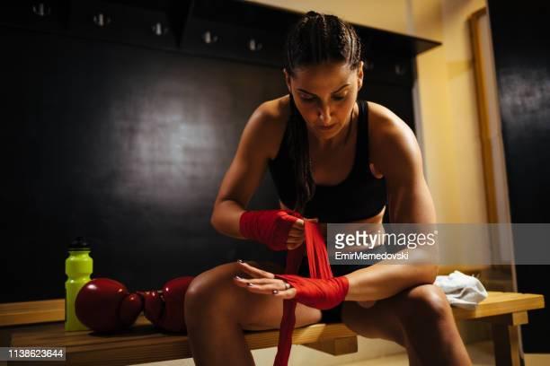 Female athlete wraps hand before kickboxing