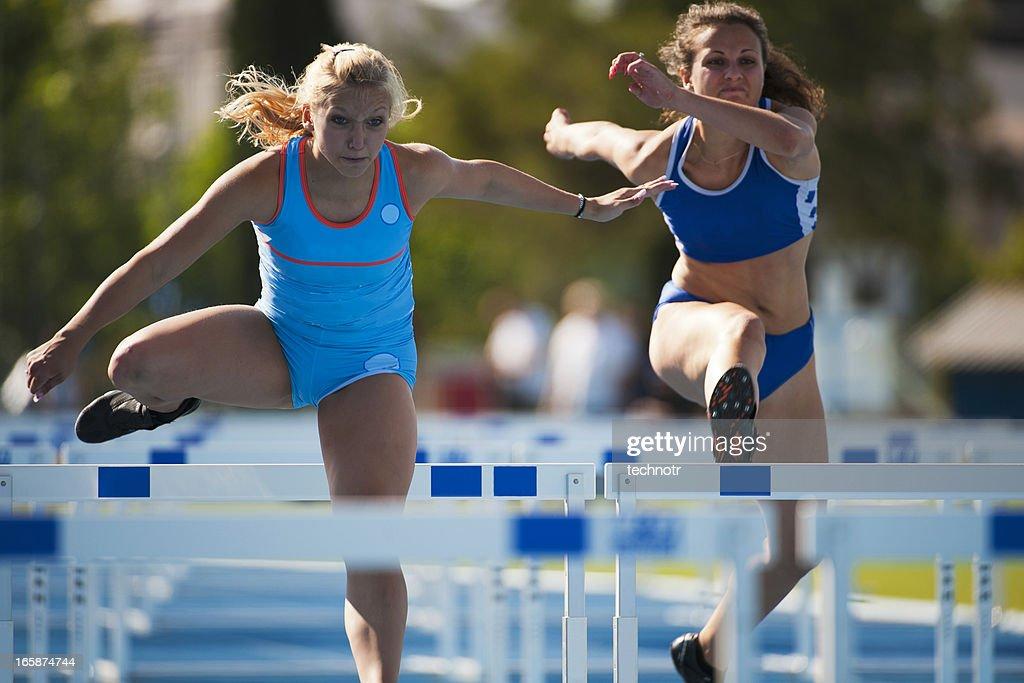 Female athletes at hurdle race : Stock Photo
