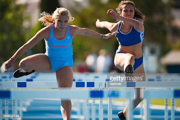 female athletes at hurdle race - womens track stock photos and pictures