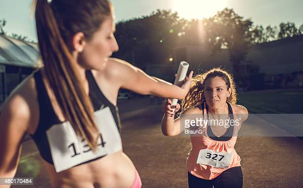 female athletes exchanging baton on a relay race. - passing sport stockfoto's en -beelden