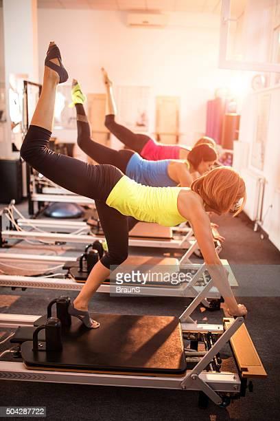 Las atletas femeninas con sus piernas ejercicio con el equipo de Pilates