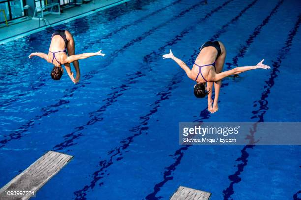 Female Athletes Jumping In Swimming Pool