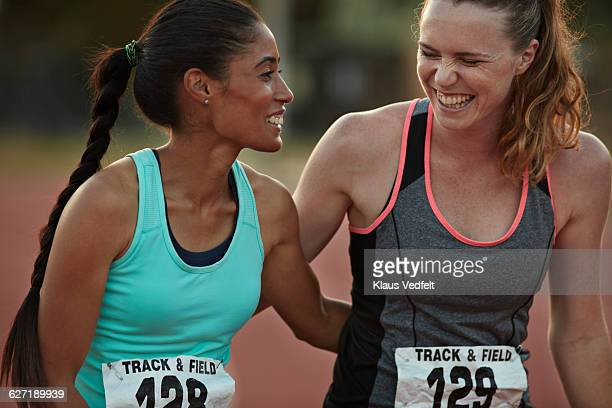 Female athletes lauging together after race