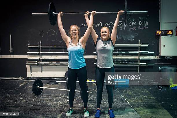 Female athletes lifting barbell at gym